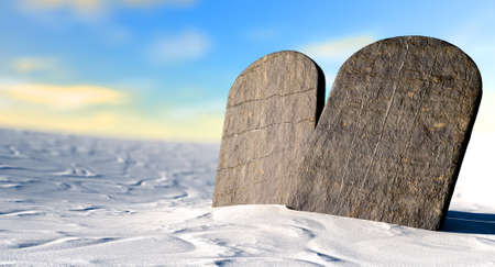 catholic: Two stone tablets representing the ten commandments standing in brown desert sand infront of a blue sky