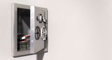 An open metal safe with bundles of british pounds on a light colored isolated wall background photo