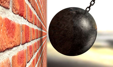 A regular metal wrecking ball attached to a chain hitting and breaking a face brick