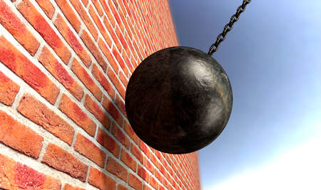 A regular metal wrecking ball attached to a chain hitting and breaking a face brick photo
