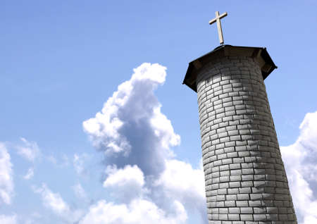 A plain stone tower turret with a wood and iron roof and a wooden crucifix on it on a blue sky background photo