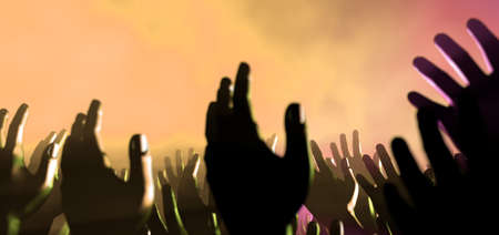 praise: A crowd level view of hands raised from the spectating crowd interspersed by colorful spotlights and a smokey atmosphere