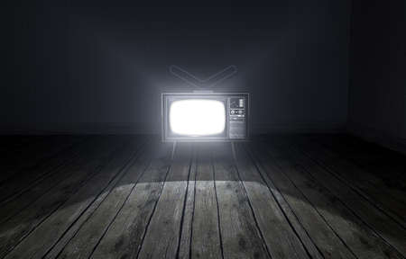 An old empty dark room with wallpaper and wooden floors and a switched on vintage television illuminating it with a spotlight effect Stock Photo