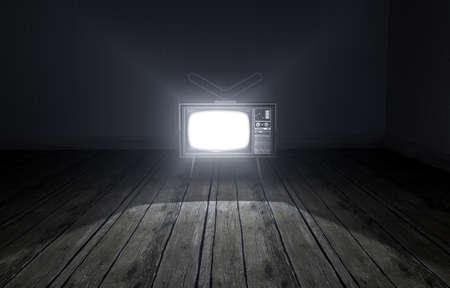 television antigua: Un viejo cuarto oscuro vacío con papel pintado y suelo de madera y encender la televisión de la vendimia iluminándola con un efecto del proyector