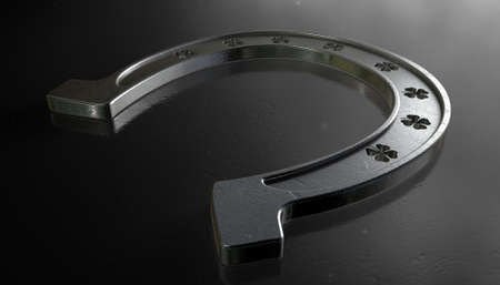 punched out: A metal horseshoe with punched out shamrock shapes on an isolated dark background