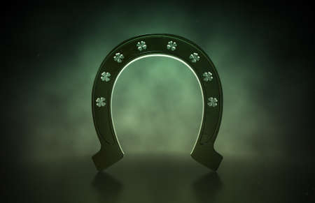 A metal horseshoe with punched out shamrock shapes on an isolated dark background photo