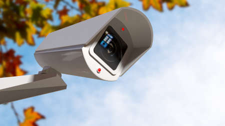 A white wireless surveillance camera with illuminated lights mounted on a wall in the daytime with copy space Stock Photo