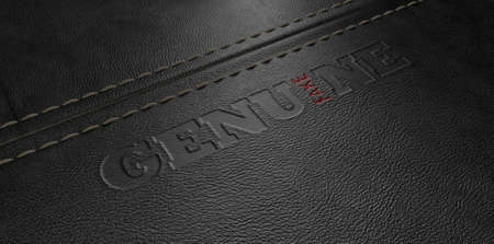 plagiarism: A concept image showing a regular stitched sheet of black leather with an embossed stamp reading genuine but the one letter reads the word fake