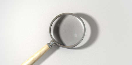 A regular magnifying glass with a wooden handle on a textured white surface photo