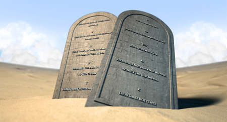 ten commandments: Two stone tablets with the ten commandments inscribed on them standing in brown desert sand infront of a blue sky