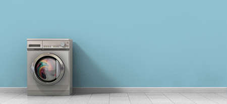 A front view of a regular brushed metal washing machine filled with clothing in an empty room with a shiny tiled floor and a baby blue wall Stock Photo