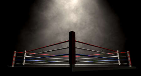 A regular boxing ring surrounded by ropes spotlit in the missle on an isolated dark background photo