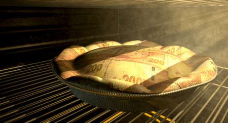 A closeup concept of a money pie made with South African Rand bank notes baking in a heated oven photo