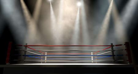 A regular boxing ring surrounded by ropes spotlit by various lights on an isolated dark background photo