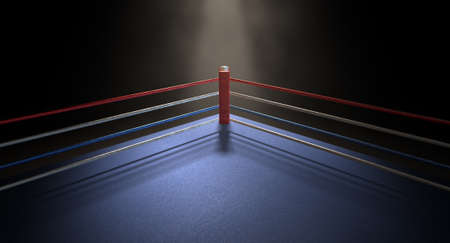 spotlit: A closeup of the red corner of a regular boxing ring surrounded by ropes spotlit by a spotlight on an isolated dark background