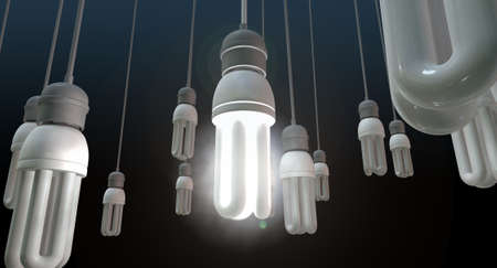 unique concept: A concept image showing unlit dangling flourescent light bulbs with one shining brighly showing leadership and innovation on an isolated dark background