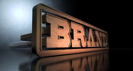 A metal cattle brand with the word brand as the marking area on an isolated dark backlit surface and background photo