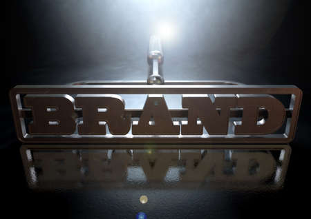 proprietary: A metal cattle brand with the word brand as the marking area on an isolated dark backlit surface and background
