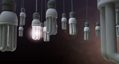 symbolism: A concept image showing unlit dangling flourescent light bulbs with one shining brighly showing leadership and innovation on an isolated dark background