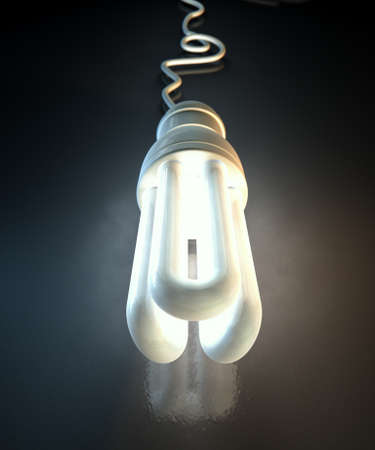 sense of space: An illuminated fluorescent light bulb connected to an electical cable laying on a dark surface with a dramatic spotlit background