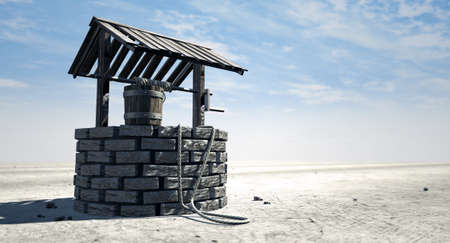 A brick water well with a wooden roof and bucket attached to a rope in a flat barren landscape with a blue sky background Foto de archivo