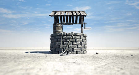 source d eau: Un puits d'eau en briques avec un toit et seau en bois attaché à une corde dans un paysage aride plat avec un fond de ciel bleu