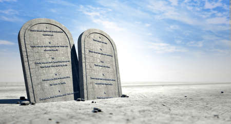 desert: Two stone tablets with the ten commandments inscribed on them standing in brown desert sand infront of a blue sky