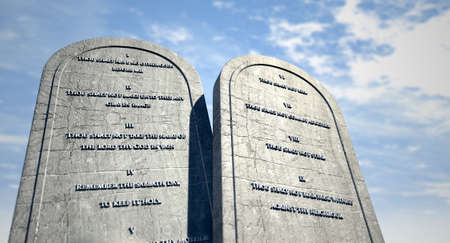 inscribed: Two stone tablets with the ten commandments inscribed on them standing in brown desert sand infront of a blue sky