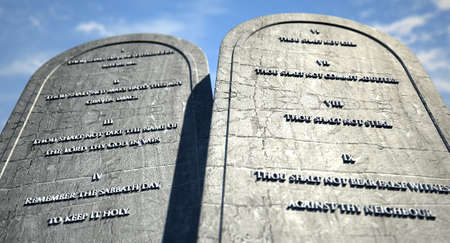 Two stone tablets with the ten commandments inscribed on them standing in brown desert sand infront of a blue sky