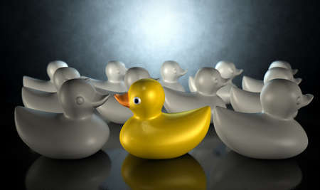 against the flow: A non-conformist depiction of a yellow rubber bath duck swimming against the flow of a group of grey rubber ducks on a dark backlit background Stock Photo