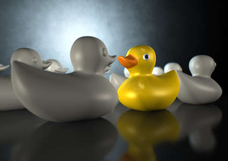A non-conformist depiction of a yellow rubber bath duck swimming against the flow of a group of grey rubber ducks on a dark backlit background Stock Photo