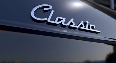 unpretentious: A closeup view of the word classic writting as a chrome emblem in a retro font