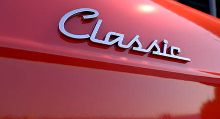 A closeup view of the word classic writing as a chrome emblem in a retro font
