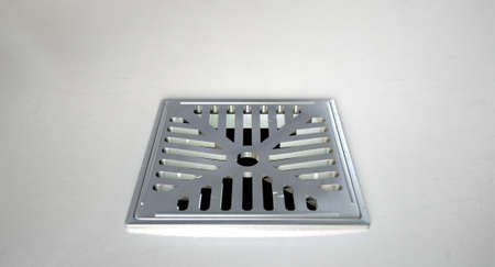 A closeup of a chrome shower drain set in on a white shower floor Imagens