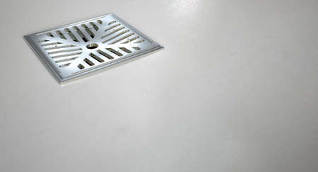 sink drain: A closeup of a chrome shower drain set in on a white shower floor Stock Photo
