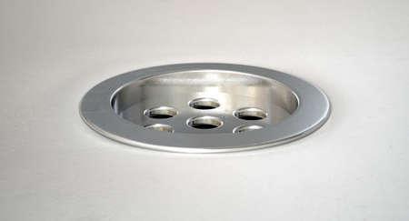 A closeup of a chrome plug hole set in a porcelain basin photo