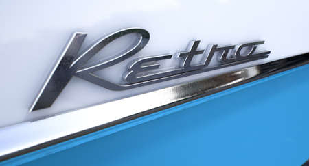 unpretentious: A closeup view of the word retro writting as a chrome emblem in a retro font set on a car painted in two tones of white and blue reflective paint seperated by a chrome trimming Stock Photo