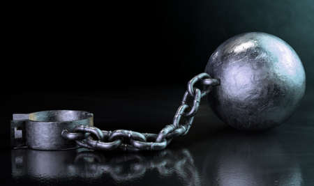restraining device: A vintage ball and chain with an open shackle on a dark backlit studio background