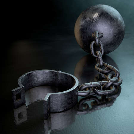 A vintage ball and chain with an open shackle on a dark backlit studio background