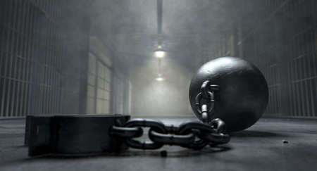incarceration: A vintage ball and chain with an open shackle on an old prison cell block floor lit by overhead lights