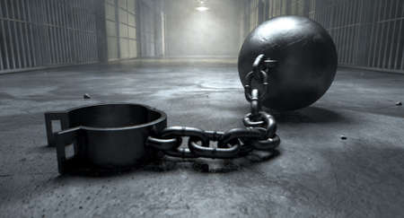 A vintage ball and chain with an open shackle on an old prison cell block floor lit by overhead lights photo