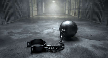 A vintage ball and chain with an open shackle on an old prison cell block floor lit by overhead lights