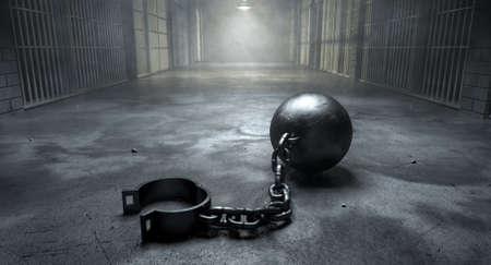 cadenas: Una bola de la vendimia y de la cadena con un grillete abierta en un viejo piso del bloque celda iluminada por las luces del techo Foto de archivo