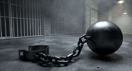 jail background: A vintage ball and chain with an open shackle on an old prison cell block floor lit by overhead lights