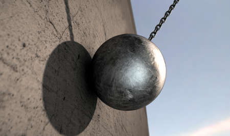 A regular metal wrecking ball attached to a chain hitting a concrete surface photo