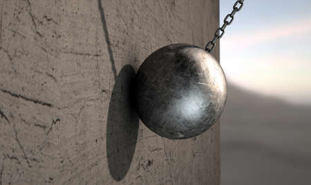 metal surface: A regular metal wrecking ball attached to a chain hitting a concrete surface Stock Photo