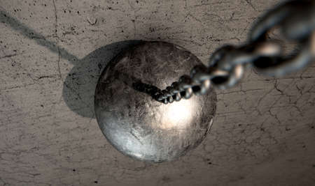 restraining: A regular metal wrecking ball attached to a chain hitting a concrete surface Stock Photo