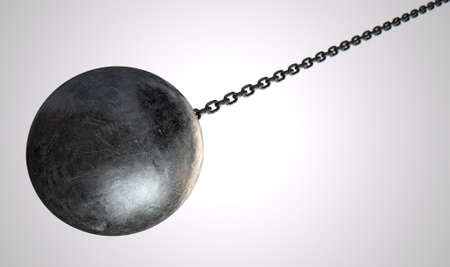 A regular metal wrecking ball attached to a chain on an isolated white background Stock Photo