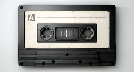 A close up view of a black vintage audio cassette tape with a white label on an isolated white background photo