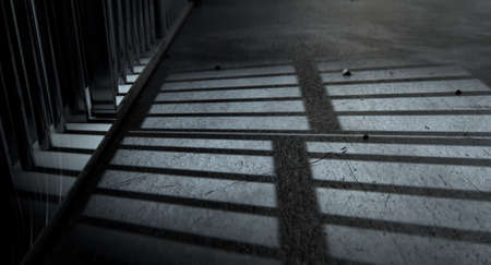 A closeup of view of a jail cells iron bars casting shadows on the prison floor with copy space